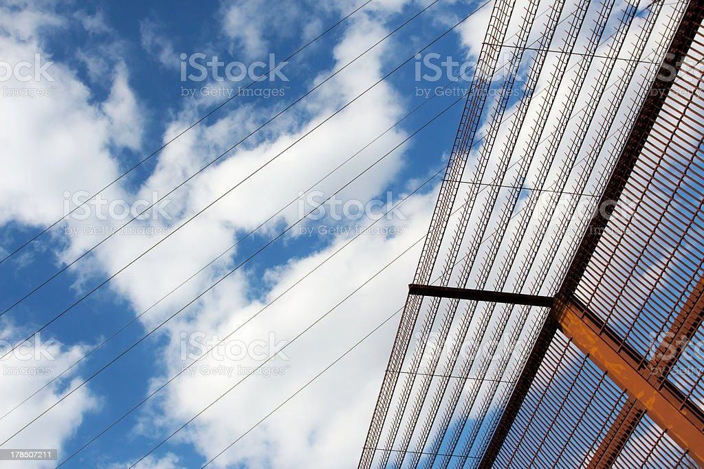 Security fence and high-voltage cables against a  blue sky royalty-free stock photo