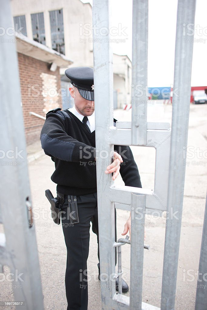 Security guard closing gate stock photo