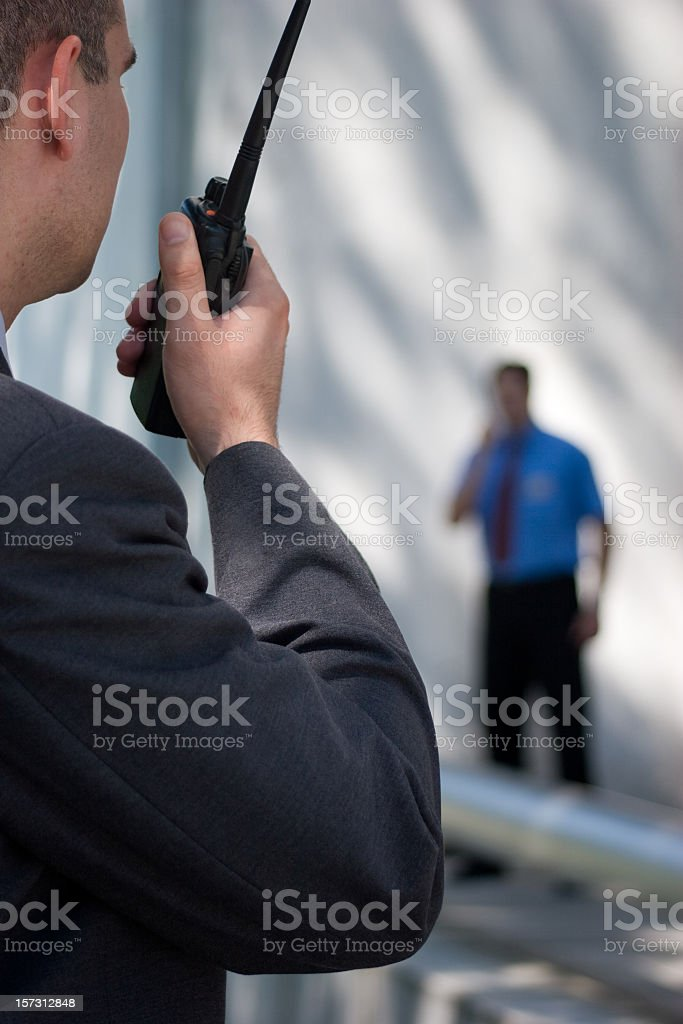 A security guard communicating with another guard stock photo