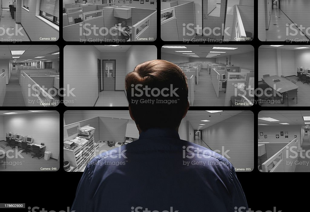 Security guard conducting surveillance by watching several monitors stock photo