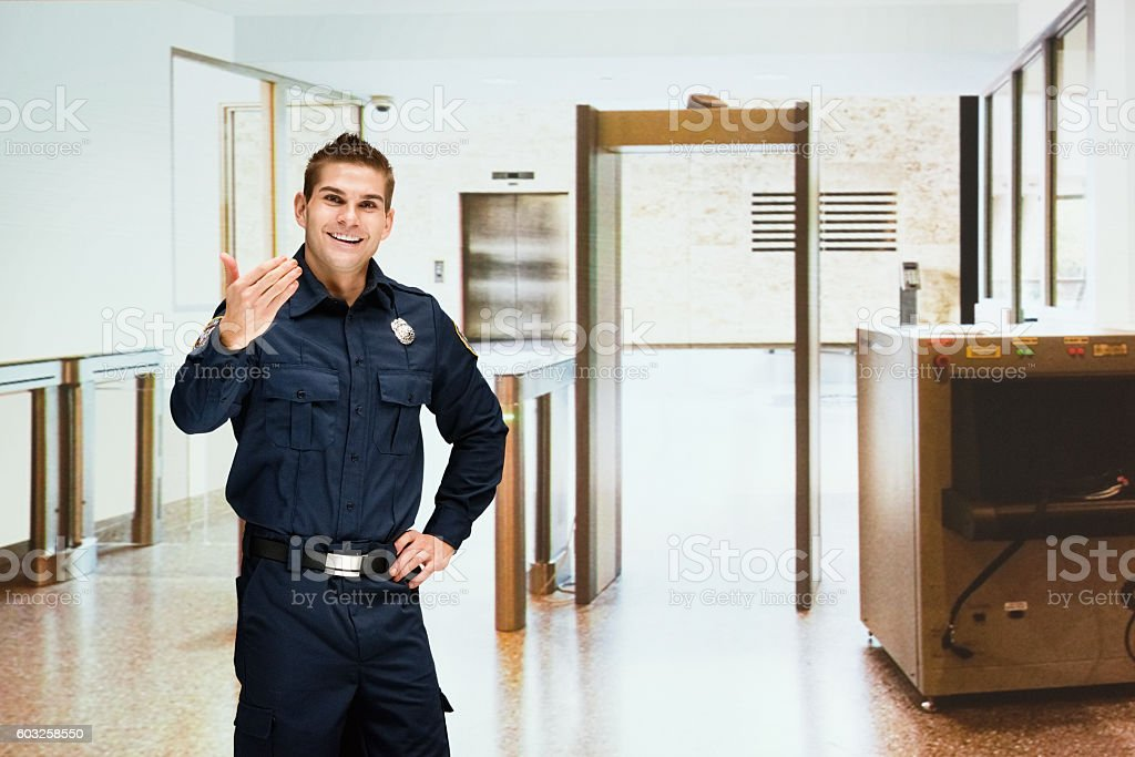 Security guard gesturing to come indoors stock photo
