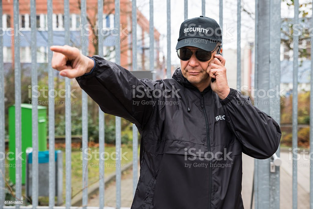 Security Guard Gesturing While Using Walkie-Talkie stock photo