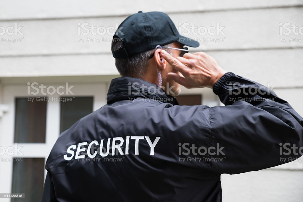 Security Guard Listening To Earpiece Against Building stock photo