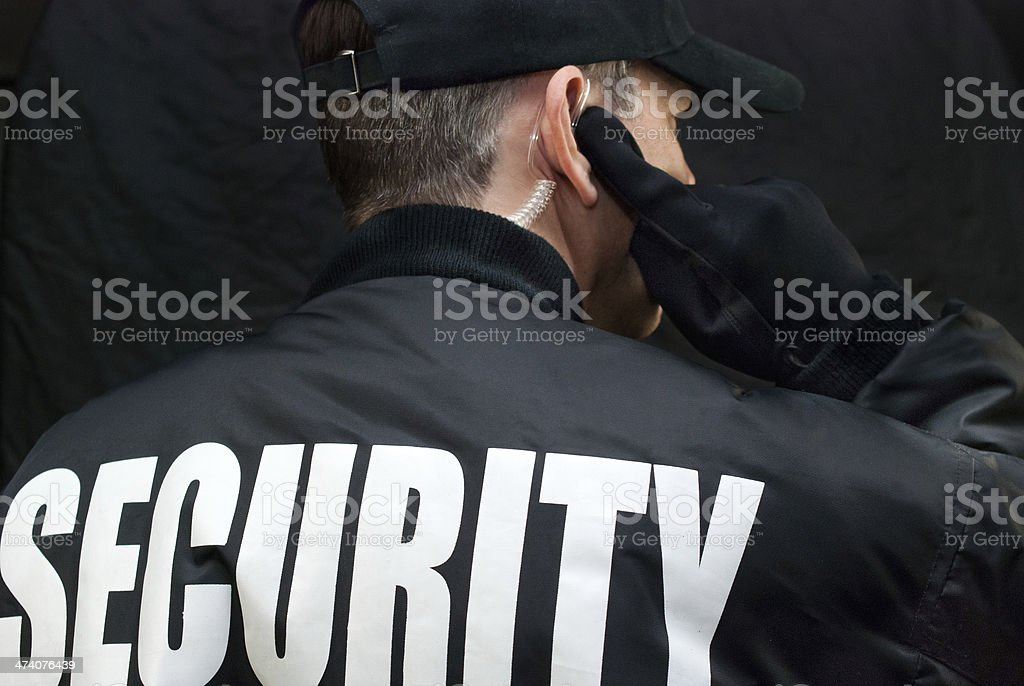 Security Guard Listens To Earpiece, Back of Jacket Showing stock photo