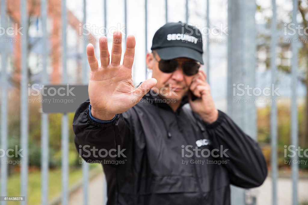 Security Guard Making Stop Gesture In Front Of Gate stock photo