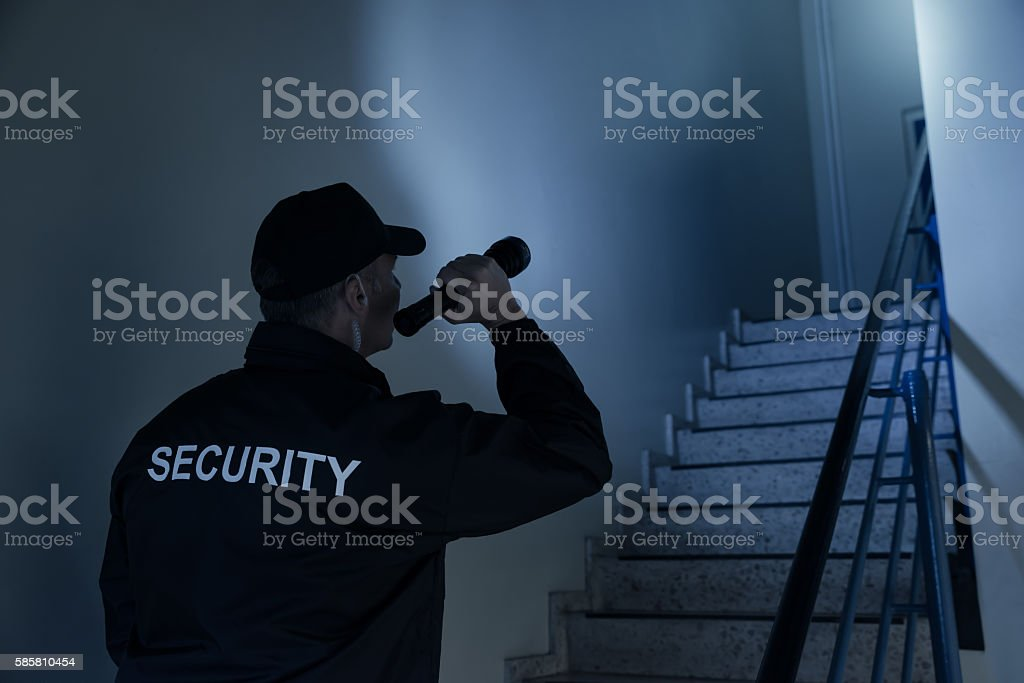 Security Guard Searching On Stairway With Flashlight stock photo