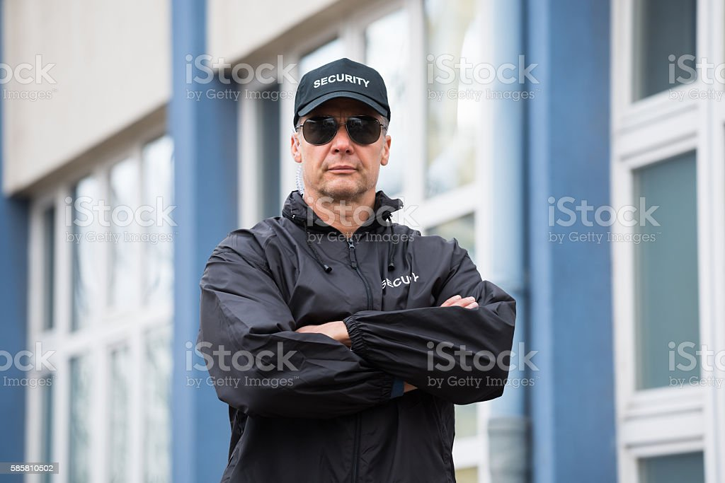 Security Guard Standing Arms Crossed Outside Building stock photo