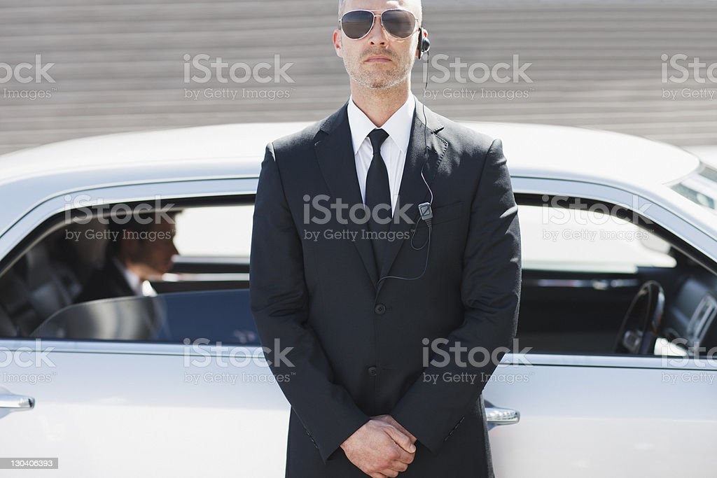 Security guard standing by car stock photo