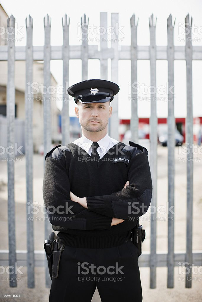 Security guard standing in front of gate stock photo