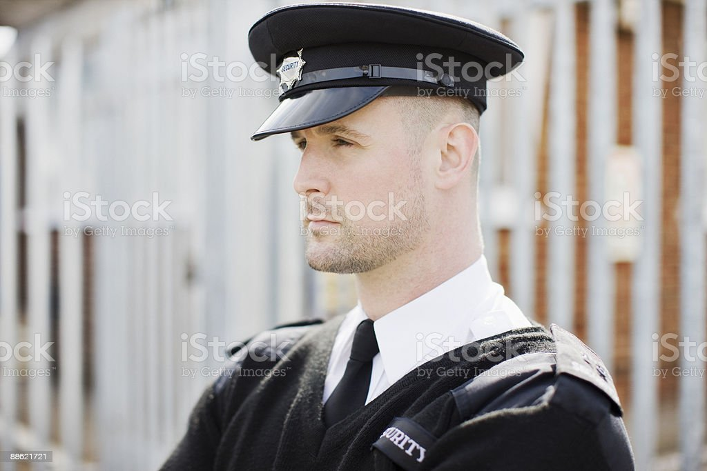 Security guard standing near fence royalty-free stock photo