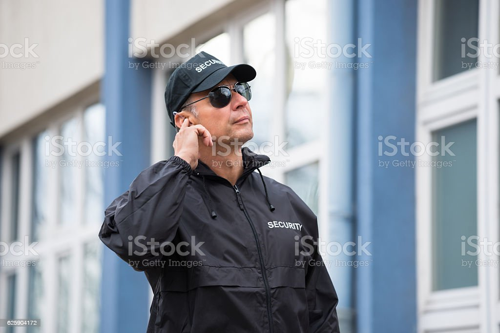 Security Guard Using Mobile Phone Outside Building stock photo