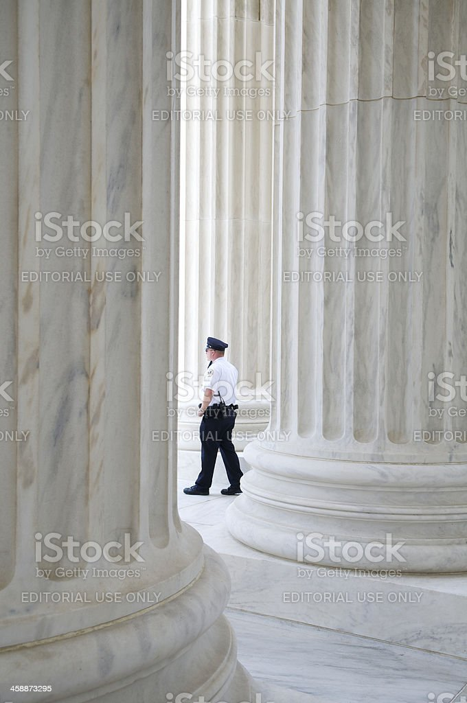 Security Guard Walks Past Column at Supreme Court Entrance royalty-free stock photo