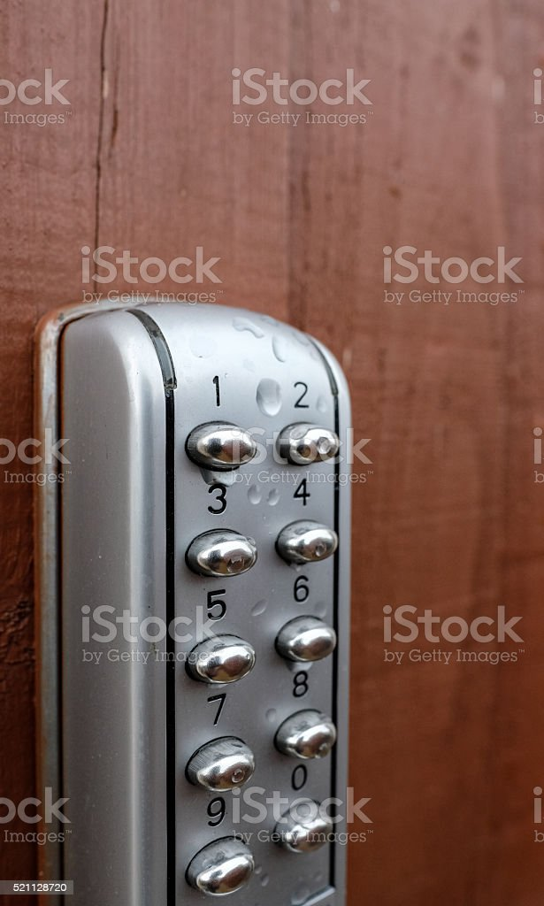 Security keypad on the panel of a wooden gate stock photo
