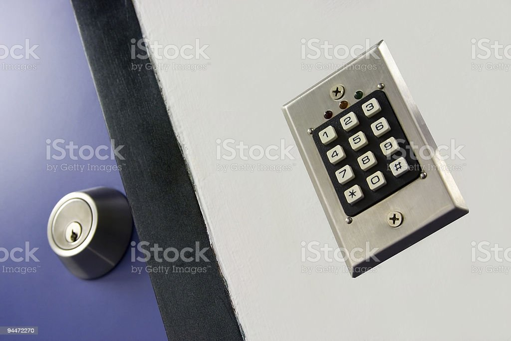 Security keypad on wall next to door with key lock royalty-free stock photo