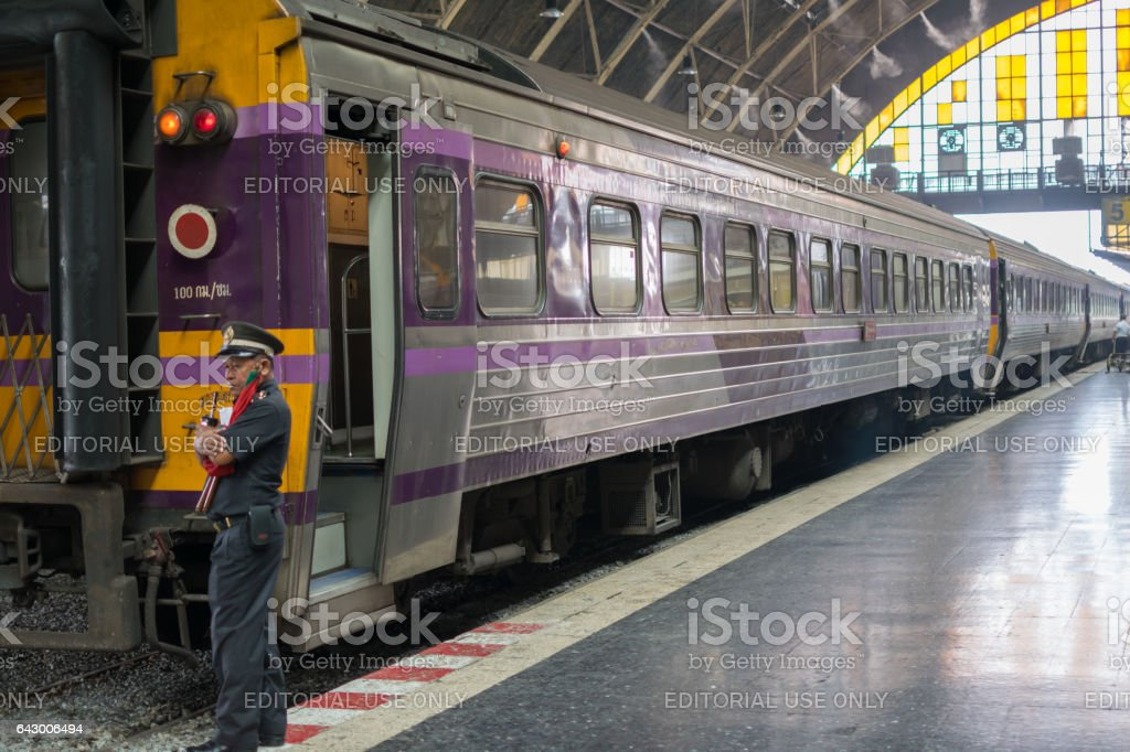 Security man at Bangkok station, Railway train on the railroad tracks in . Many people in Thailand popular travel by train because it is cheaper. stock photo
