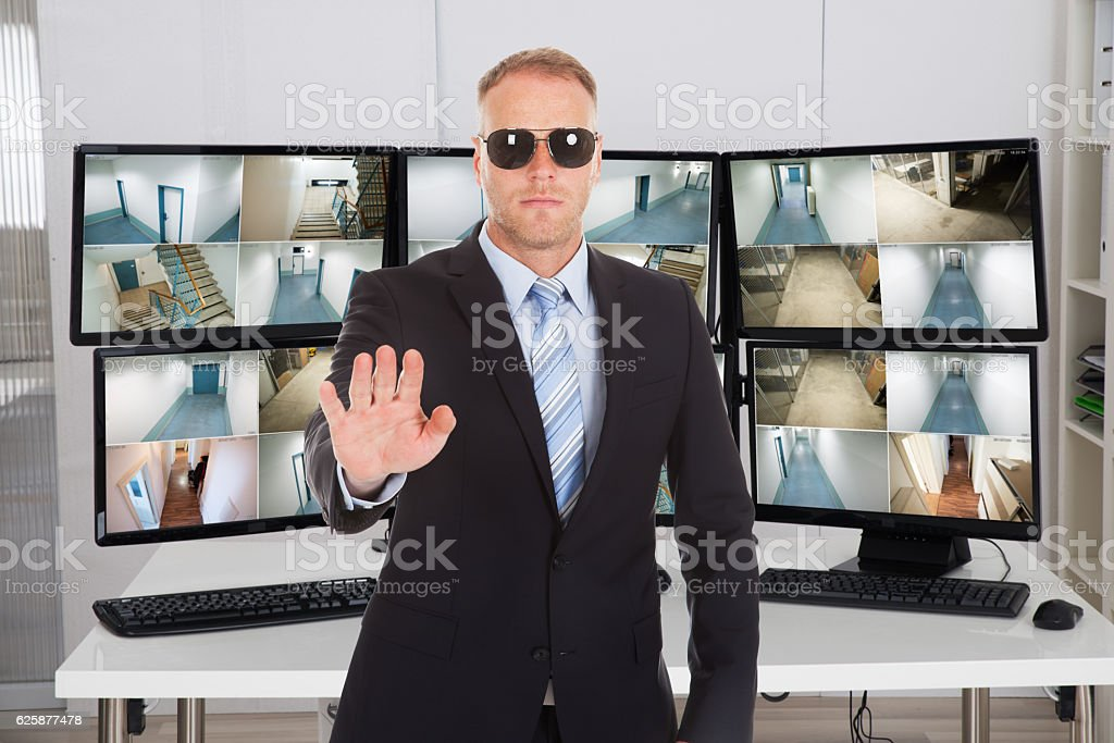 Security Manager Gesturing Stop Sign Against Monitors stock photo