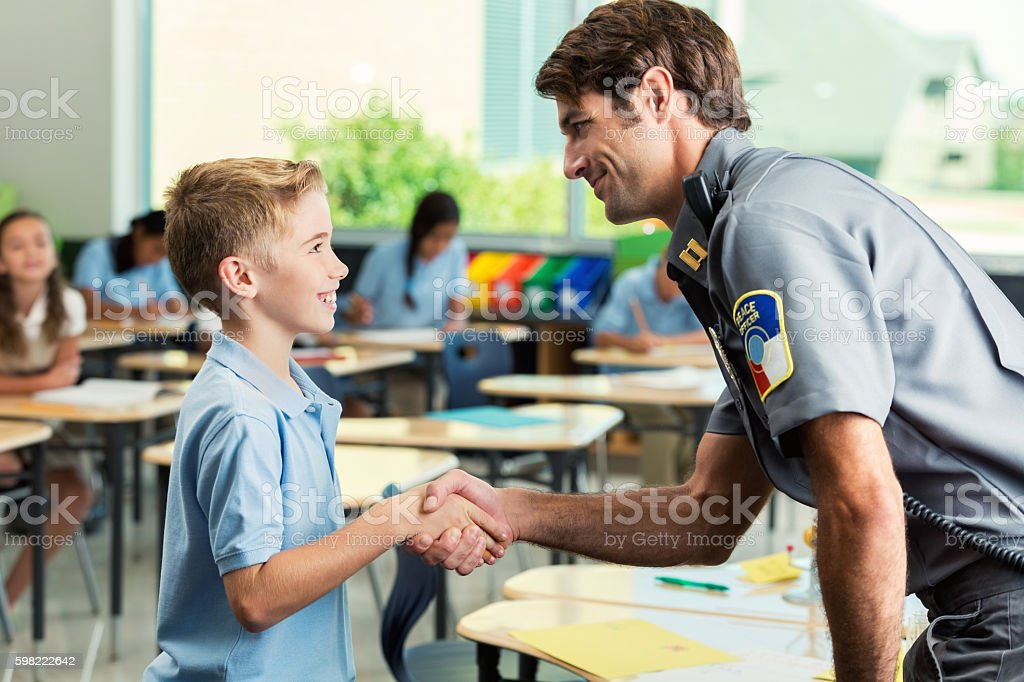 Security officer greets elementary age private school student stock photo
