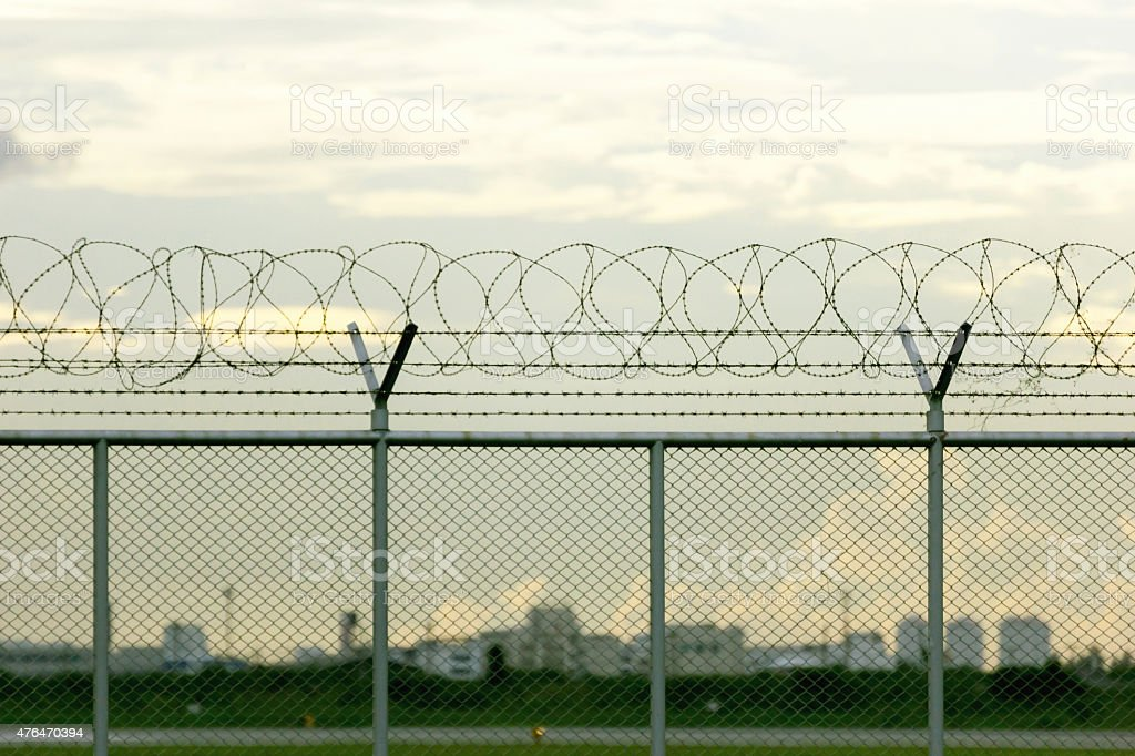 security restricted area with a barbed wire fence stock photo