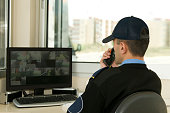 Security worker speaking on radio while watching monitor