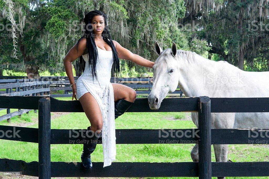 Seductive black woman with horse stock photo