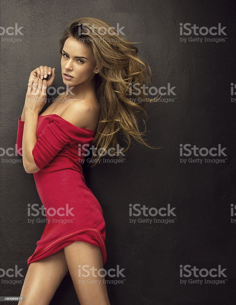 Seductive blond woman in red dress stock photo