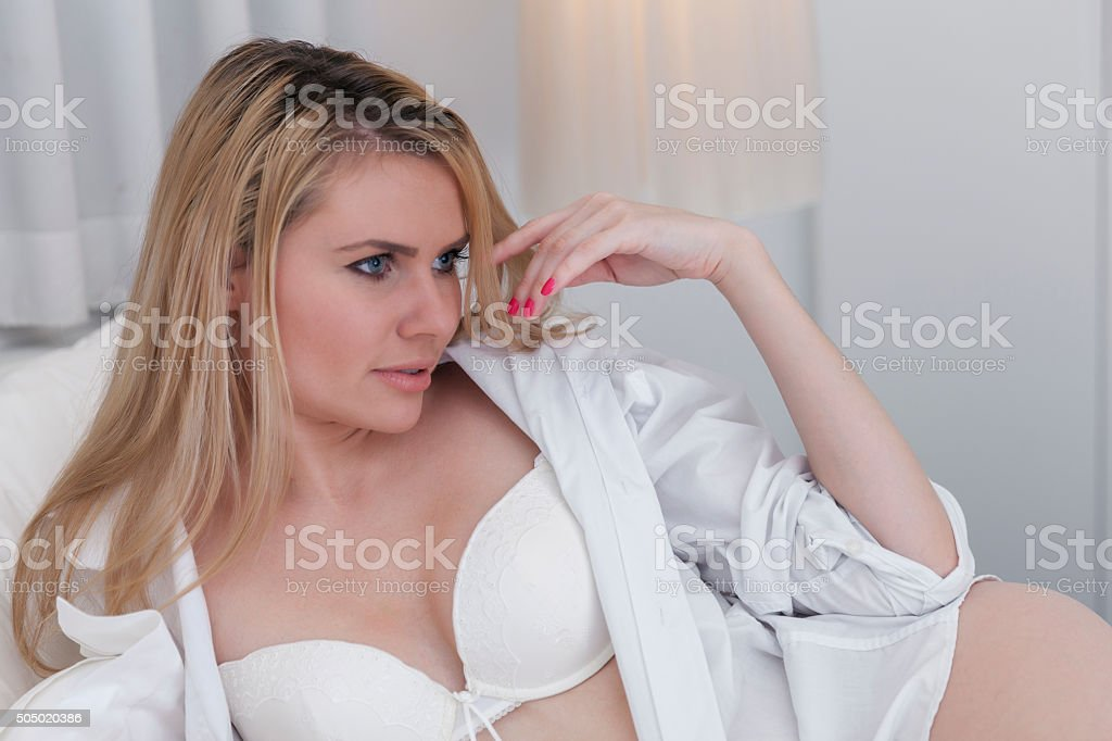 Seductive smirkng blonde lying on bed in man's shirt stock photo