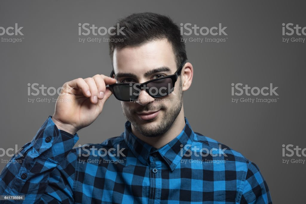 Seductive young man taking off sunglasses smiling at camera stock photo