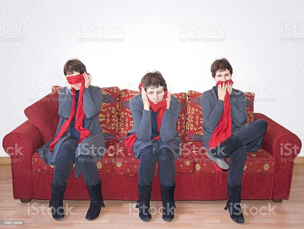 See no evil, hear no_evil, speak_no evil.Mature woman on sofa. stock photo