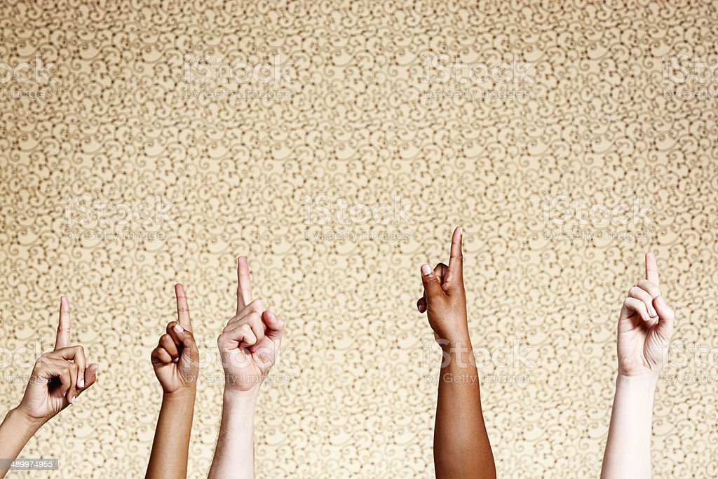 Five mixed hands point upwards enthusiastically against a patterned...