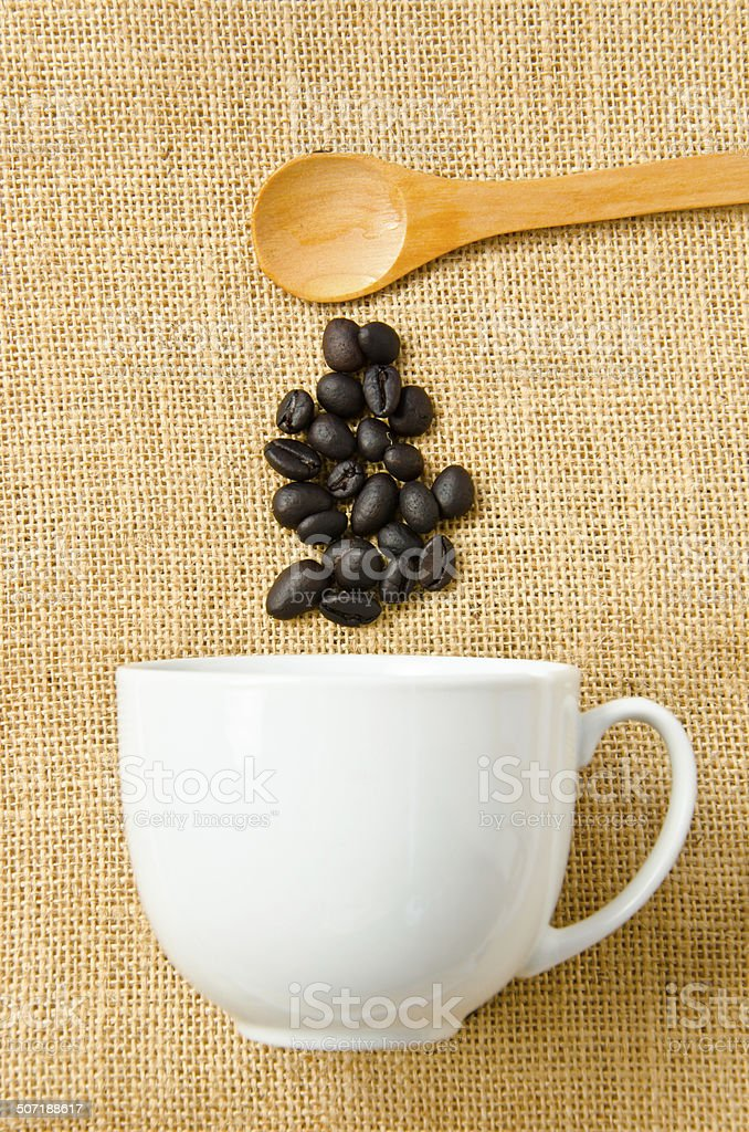 Seed coffee, wooden spoon and a cup of coffee. royalty-free stock photo