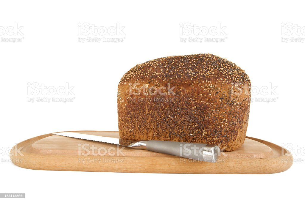 Seeded wholemeal loaf of Bread with knife on wooden board stock photo