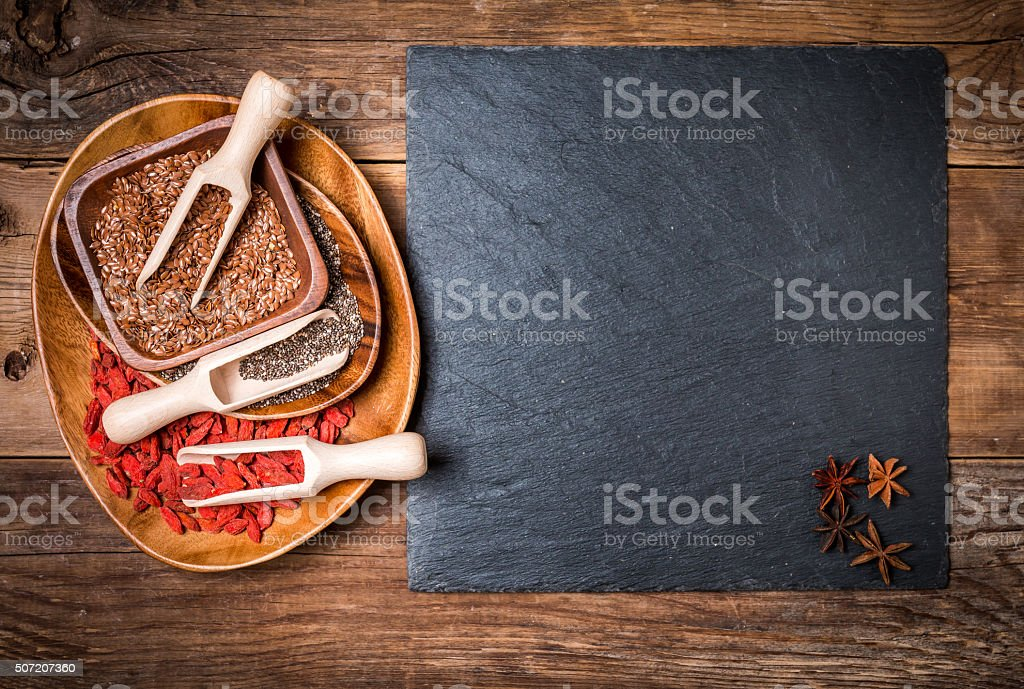 Seeds and goji in a wooden spoons stock photo
