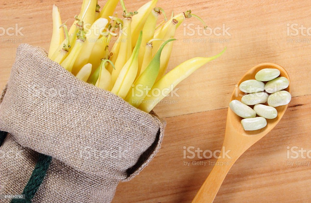 Seeds and heap of yellow beans in jute bag stock photo