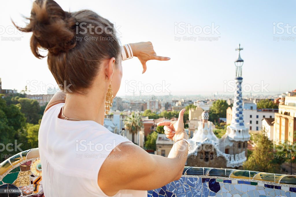Seen from behind woman framing with hands in Park Guell stock photo