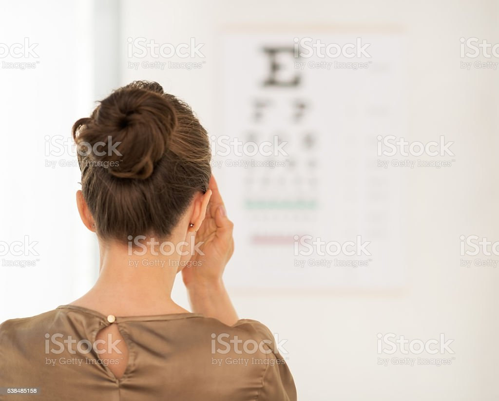 Seen from behind woman testing vision with Snellen chart stock photo