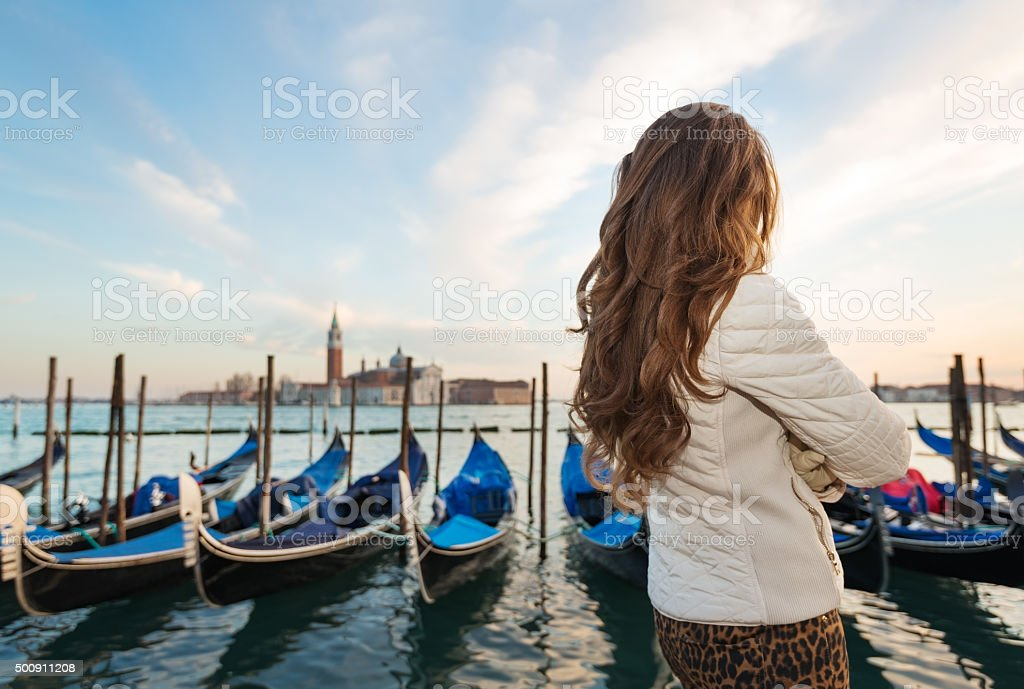 Seen from behind, woman traveler standing on embankment, Venice stock photo