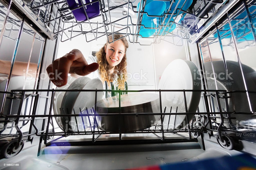 Seen from inside dishwasher, cute smiling girl loading or unloading stock photo