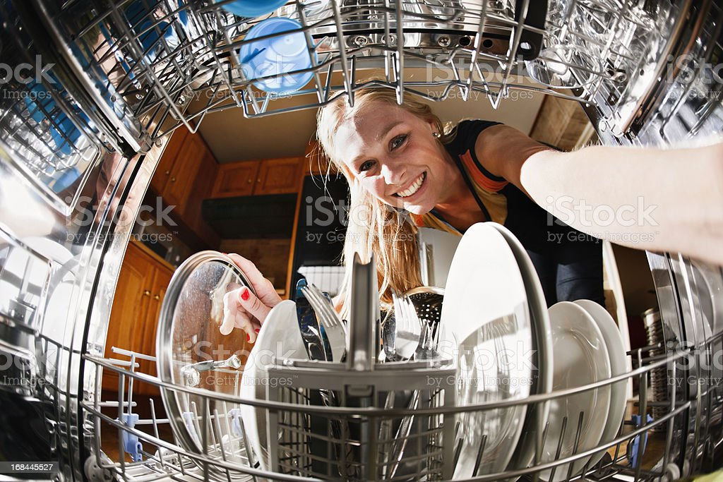 Seen from inside drum, pretty blonde loads the dishwasher royalty-free stock photo
