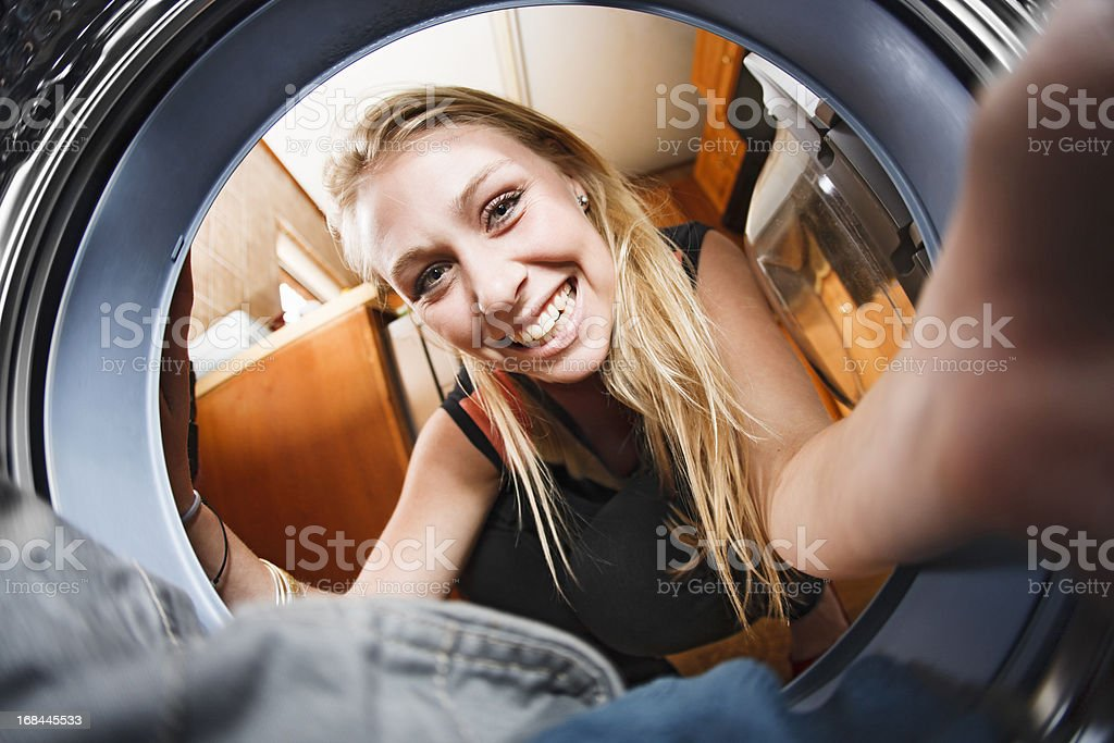 Seen from inside the washing machine,  pretty blonde loads laundry royalty-free stock photo