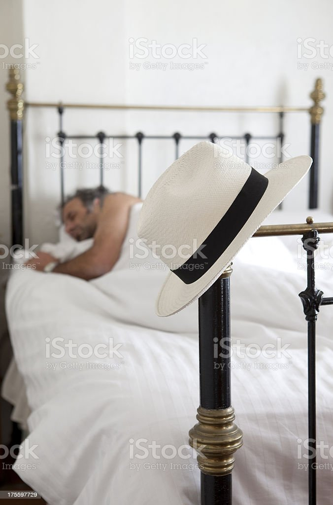 Seeping man with a hat on the bedpost royalty-free stock photo