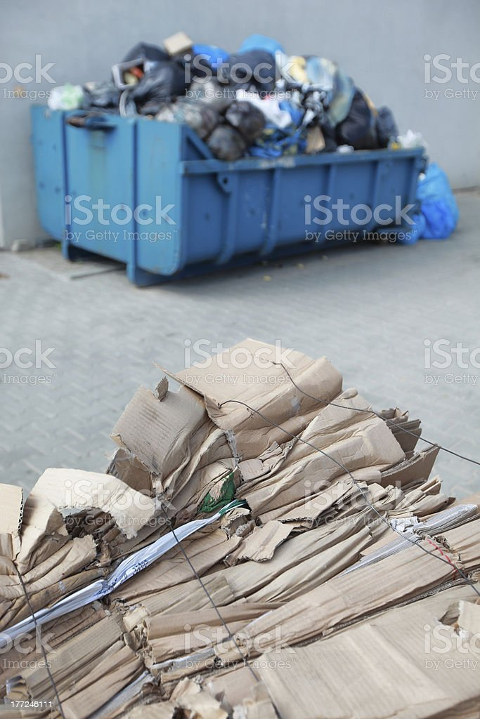 segregated cardboard at the front, waste containers with nonsorted wasted royalty-free stock photo