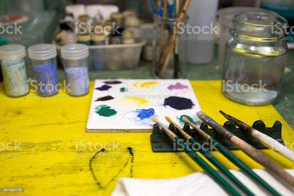Selected focus paintbrushes and blue color on palette with paint stock photo