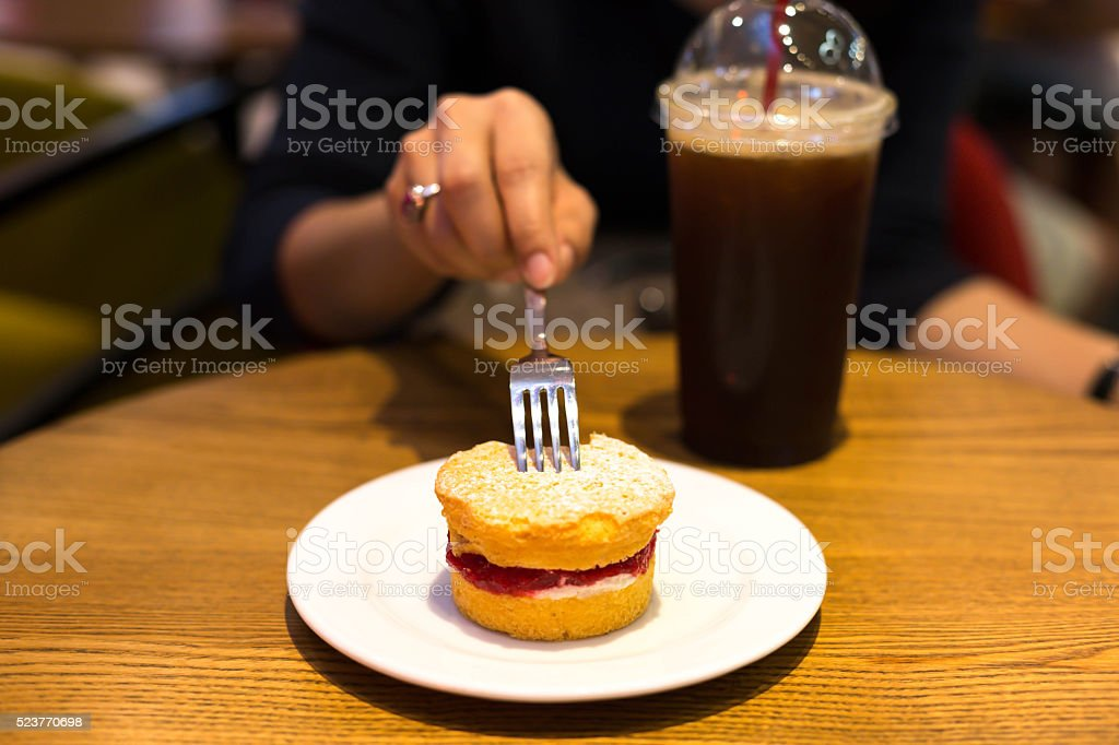 Selected Focus woman holding fork eating scone with iced coffee stock photo