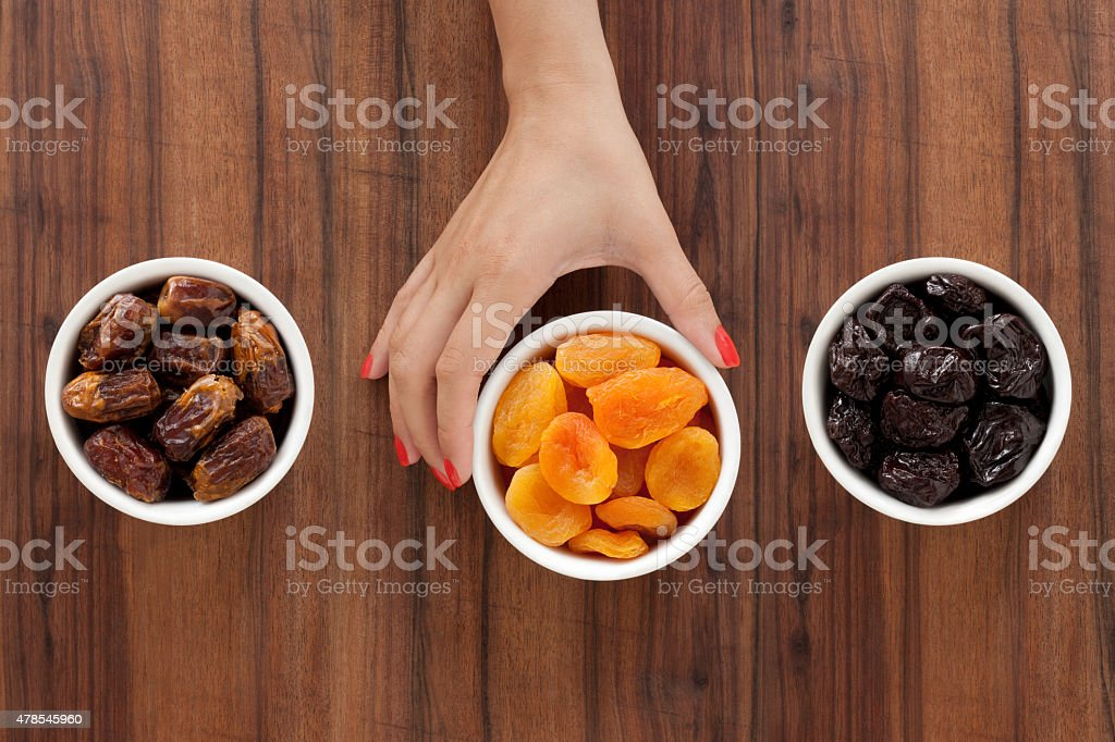 Selecting dried fruits stock photo