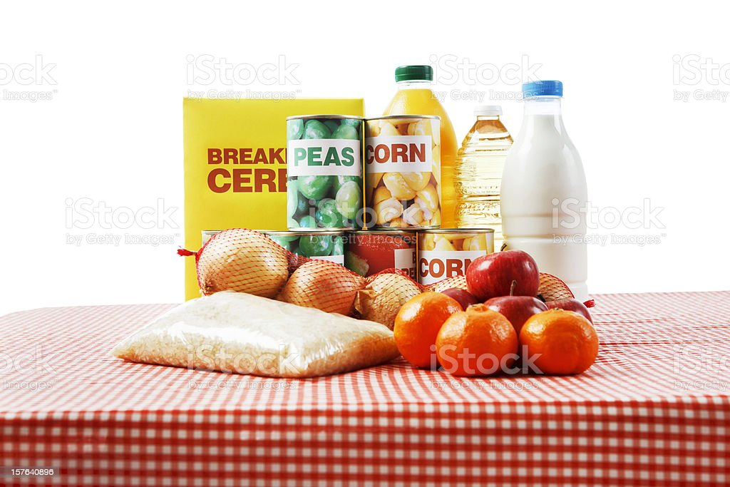 Selection of basic foods on gingham cloth isolated against  white stock photo