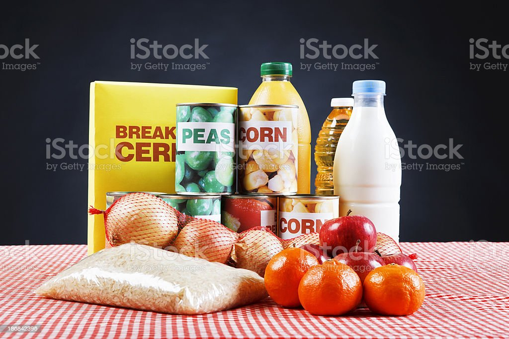 Selection of basic foods on red tablecloth against black royalty-free stock photo