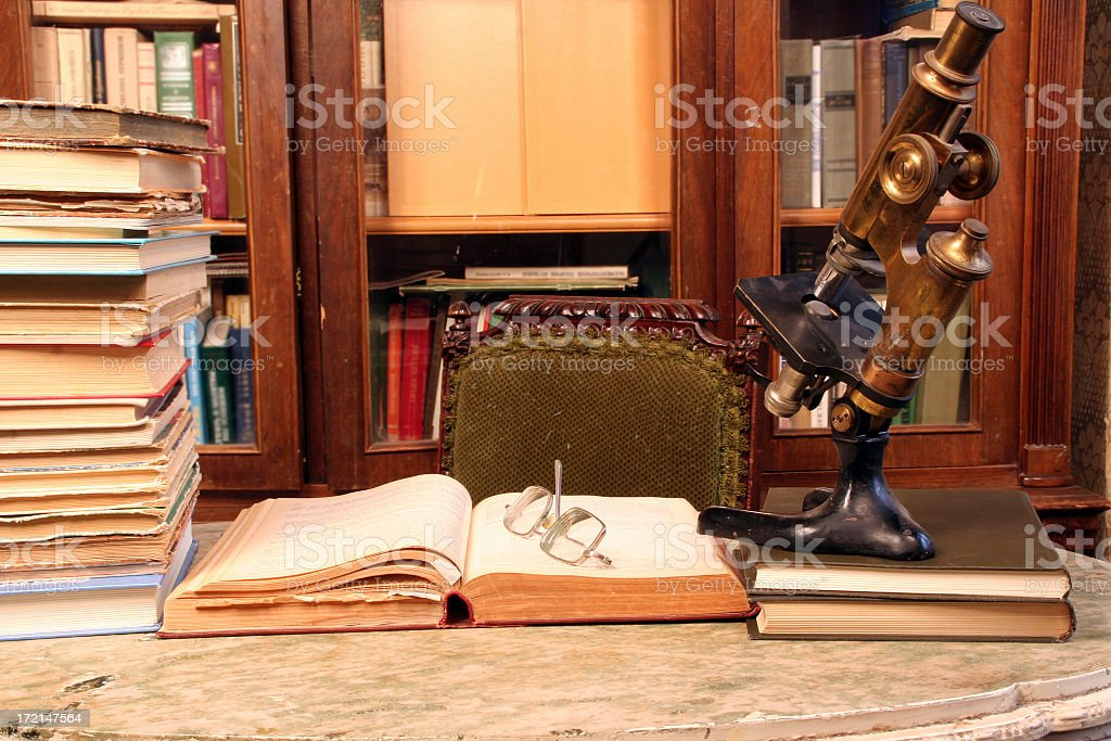 A selection of books in a library next to a telescope stock photo