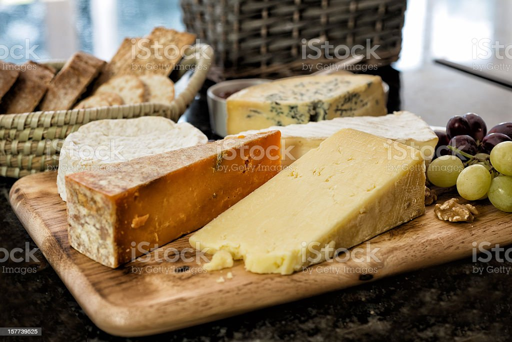 Selection of English and French Cheese on Rustic board stock photo