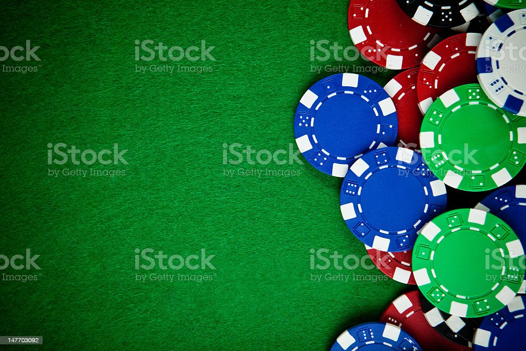 Selection of gambling chips on a green cloth stock photo