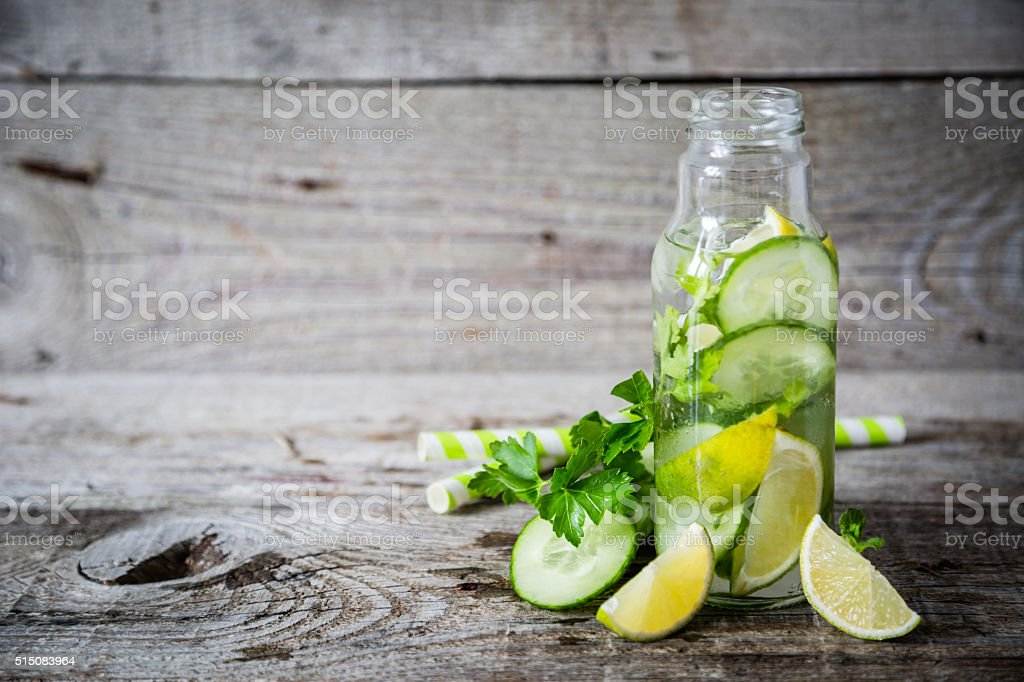 Selection of infused water in glass bottles, rustic wood background stock photo